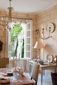 Shabby-chic dining room in nostalgic, romantic French country house; view through open lattice window into courtyard with planters