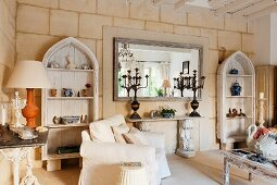 Limestone wall with shabby-chic wooden shelves, console table and mirror in restored, French country house