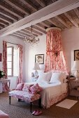 Romantic, shabby-chic bedroom with red and white Toile de jouy fabric curtains, bedroom bench, scatter cushions and canopy below rustic, wood-beamed ceiling