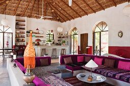 Lounge area with colourful seat cushions on masonry benches in open-plan interior with palm thatch roof