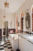 Spacious bathroom with bathtub, arched French windows and chequered floor
