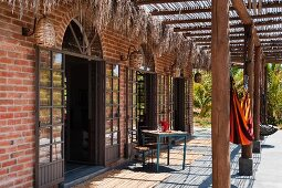 Sunny terrace with pergola outside house with arched, lattice French windows in brick facade