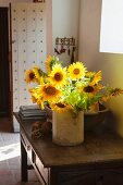 Vase of sunflowers on wooden console table in foyer