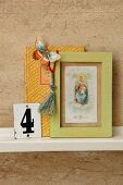 Vintage ornaments on bookshelf - paper butterfly on decorative book, Tibetan prayer tassels on framed picture of the Madonna and old enamel sign with the number 4
