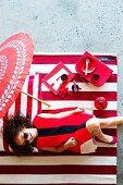 Rote Mädchenaccessoires und Spielsachen auf rot-weiss gestreiftem Teppich; darauf ein lachendes Mädchen im roten Kleid