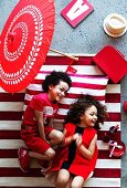 Laughing children dressed in red on red and white striped rug