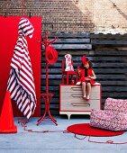 Wohnaccessoires und Möbel in kräftigem Rot; dazwischen ein Mädchen im roten Kleid auf einer Kommode sitzend