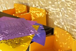 Yellow chairs, table and sheets of coloured paper against an exterior wall (Eric Linard art gallery, France)