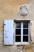 Old window in weathered house facade (Eric Linard art gallery, France)