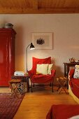 Seating area in shades of red with chair, sofa & cupboard in village house (Eggelingen, Ostfriesland, Germany)