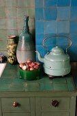 Alter Wasserkessel, Vasen & Zwiebeln in Schale auf gefliester Küchenablage