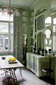 Wohnraum in Mintgrün mit ausgefallener, raumhoher Spiegelsammlung