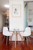Sitzplatz vor Wandpfeiler mit Designermöbeln auf edlem Parkett; Einblick in den Schlafbereich und auf der anderen Seite in den Küchenbereich