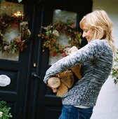 Young woman holding logs outside country-house-style front door decorated with autumnal wreaths