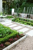 Symmetrical garden with clearly defined beds of flowers and vegetables and stone flags laid in gravel path