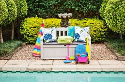 Toys in front of monks' bench on side of pool in garden