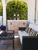 Weathered wooden table, sofa with wicker frame and cane trunk on veranda