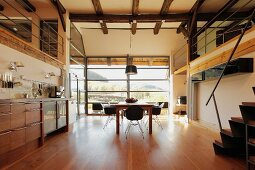 Open-plan kitchen with dining area in renovated farmhouse; panoramic window in background
