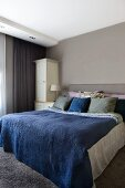 Double bed with blue bedspread in bedroom painted pale grey