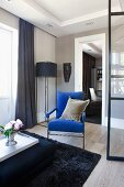 Vase of flowers on tray on ottoman and blue armchair in lounge area; standard lamp in corner