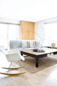 Bright living room with wooden table, classic rocking chair and sofa