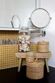 Small arrangement of woven containers and collection of shells against mosaic tiles; black washstand, mirrored cabinet and magnifying mirror on jointed arm