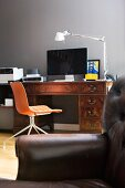 Delicate office chair with orange shell seat, antique writing desk and designer table lamp behind leather armchair