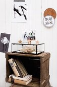 Books in stacked, vintage wooden crates and black and white decor on vertical wooden cladding