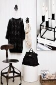 Fashion-inspired, vintage still-life arrangement with swivel chair, bag on bin and dress and scarf hanging on hooks on white wall panelling