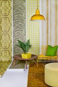 House plant on wooden table, yellow chair and pouffe in front of lengths of wallpaper