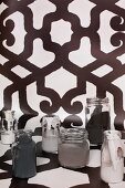 Various monochrome paints in glass jars on length of black and white patterned wallpaper