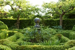 Sculpture surrounded by mature plants amongst clipped box hedges in sunny garden