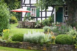 Seating area with parasol in front of renovated, old, half-timbered house in idyllic garden with low, dry stone wall