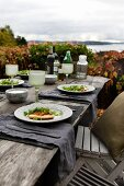 Autumnal atmosphere; pizza and salad on table with rustic place settings and view of Norwegian skerry coast