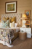 Double bed with beige, quilted headboard flanked by antique bedside lamps on white bedside cabinets