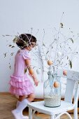 Little girl in pink dress behind Easter bouquet of white-painted spring branches