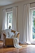 Comfortable wicker chair in front of windows with over-long curtains