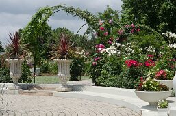 Fürstlicher Garten mit rankenden Rosen; im Vordergrund bepflanzte Steinpokale und -schalen