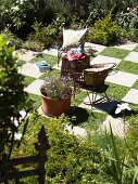 Delicate garden furniture and large terracotta planter of flowers on chequered pattern of stone slabs and squares of lawn