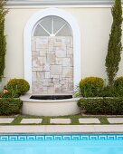 Arched window filled with mosaic of stone tiles and small fountain
