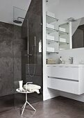 Contemporary bathroom with shower area behind glass partition