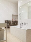 White-tiled bathroom with large mirror above bathtub and leopard-patterned towels