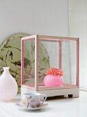Kunstobjekt in Glaskästchen, bemalter Keramikteller mit Vogelmotiv, Glasvase und Teetasse auf weisser Ablage