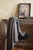 Massiver Holztisch mit filigranem Metallstuhl mit darüberhängender grauer Wolldecke