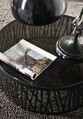 Runder Beistelltisch mit Glasplatte auf grauem Teppich; auf dem Tisch ein aufgeschlagenes Buch und eine Lesebrille