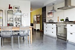 Long kitchen counter with drawer units and stainless steel elements in open-plan interior
