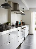 Long kitchen counter with stainless steel worksurface and pendant lamps with metal lampshades