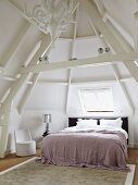 Tower room with double bed under skylight; bedside lamp with silver lampshade on bedside table