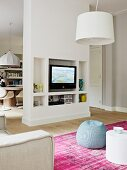 Living-dining room with white partition; TV and ornaments in niches