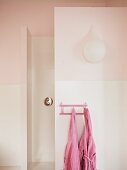 Teardrop-shaped sconce lamp on pink bathroom wall; two pink children's bathrobes hanging on small peg rack